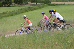 Couples riding bicycles on rural path stock images