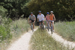Couples riding bicycles on rural path stock photos