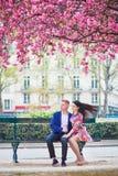 Couples romantiques à Paris avec des arbres de fleurs de cerisier Photo stock