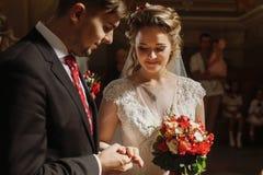 Couples romantiques échangeant des anneaux pendant la cérémonie de mariage dans le chur Photos stock