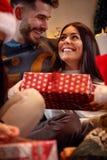 Couples romantiques échangeant des boîte-cadeau au réveillon de Noël Image libre de droits