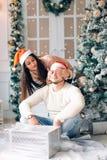 Couples romantiques échangeant des cadeaux de Noël à la maison Images libres de droits