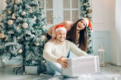 Couples romantiques échangeant des cadeaux de Noël à la maison Photos libres de droits