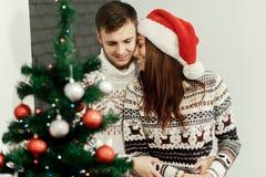 Couples romantiques étreignant, belle fille de brune dans Santa rouge ha Images stock