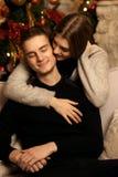 Couples romantiques étreignant dans l'intérieur de Noël Photos stock