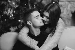 Couples romantiques étreignant dans l'intérieur de Noël Image libre de droits