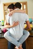 Couples romantiques étreignant dans la cuisine photos stock