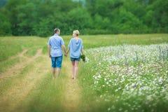 Couples romantiques étreignant et respirant l'air frais dans un domaine chaud avec les fleurs daizy image stock