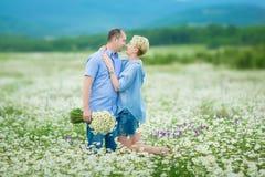 Couples romantiques étreignant et respirant l'air frais dans un domaine chaud avec les fleurs daizy photographie stock libre de droits