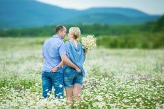 Couples romantiques étreignant et respirant l'air frais dans un domaine chaud avec les fleurs daizy photos stock