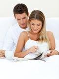 Couples romantiques affichant un journal Images stock