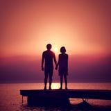 Couples romantiques appréciant le coucher du soleil en mer Images stock