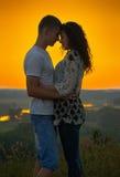 Couples romantiques au coucher du soleil sur le fond jaune lumineux de ciel, amour Photos libres de droits