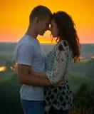 Couples romantiques au coucher du soleil sur le fond jaune lumineux de ciel, concept de tendresse d'amour, jeunes adultes Image libre de droits