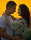 Couples romantiques au coucher du soleil sur le fond jaune lumineux de ciel, concept de tendresse d'amour, jeunes adultes Images libres de droits