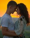 Couples romantiques au coucher du soleil sur le fond jaune lumineux de ciel, concept de tendresse d'amour, jeunes adultes Photo libre de droits