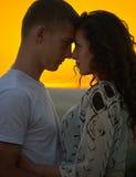 Couples romantiques au coucher du soleil sur le fond jaune lumineux de ciel, concept de tendresse d'amour, jeunes adultes Photographie stock