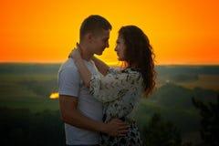 Couples romantiques au coucher du soleil sur le fond jaune lumineux de ciel, concept de tendresse d'amour, jeunes adultes Photos libres de droits