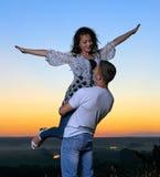 Couples romantiques ayant l'amusement au coucher du soleil sur le paysage extérieur et beau et le ciel jaune lumineux, concept de Photo libre de droits