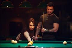 Couples romantiques ayant l'amusement jouant le billard Photographie stock libre de droits