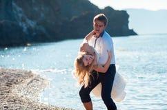 Couples romantiques ayant l'amusement sur la plage Jeunes dans l'amour, l'homme attirant et la femme appréciant égaliser, tenant  Photos libres de droits
