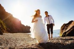 Couples romantiques ayant l'amusement sur la plage Jeunes dans l'amour, l'homme attirant et la femme appréciant égaliser, tenant  Photographie stock libre de droits