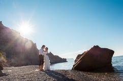 Couples romantiques ayant l'amusement sur la plage Jeunes dans l'amour, l'homme attirant et la femme appréciant égaliser, tenant  Images stock