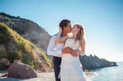 Couples romantiques ayant l'amusement sur la plage Jeunes dans l'amour, l'homme attirant et la femme appréciant égaliser, tenant  Image stock