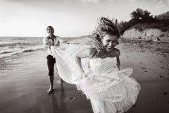 Couples romantiques ayant l'amusement sur la plage Jeunes dans l'amour, l'homme attirant et la femme appréciant égaliser, tenant  Photo libre de droits