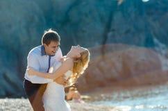 Couples romantiques ayant l'amusement sur la plage Jeunes dans l'amour, l'homme attirant et la femme appréciant égaliser, tenant  Images libres de droits