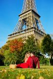 Couples romantiques ayant le pique-nique sur l'herbe pr?s de Tour Eiffel photographie stock libre de droits