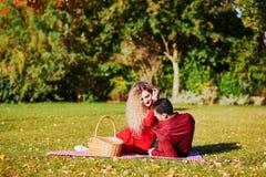 Couples romantiques ayant le pique-nique sur l'herbe un jour d'automne photos libres de droits