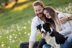 Couples romantiques chez les chiens de marche d'amour dans la nature et le sourire Photo stock