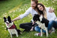 Couples romantiques chez les chiens de marche d'amour dans la nature et le sourire Images stock