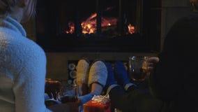 Couples romantiques détendant devant un feu Photographie stock