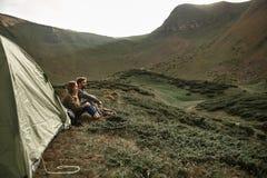 Couples romantiques détendant près de la tente tout en étant dans les montagnes photos libres de droits