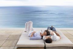 Couples romantiques détendant sur des lits pliants par la piscine d'infini Photo stock