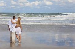 Couples romantiques d'homme et de femme embrassant sur une plage Photo stock