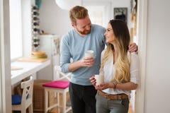 Couples romantiques dans l'amour à la maison buvant le café et le sourire Image libre de droits