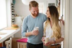 Couples romantiques dans l'amour à la maison buvant le café et le sourire images stock