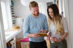 Couples romantiques dans l'amour à la maison buvant le café et le sourire Photos stock