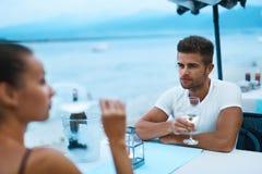 Couples romantiques dans l'amour dînant au restaurant de plage de mer Image stock