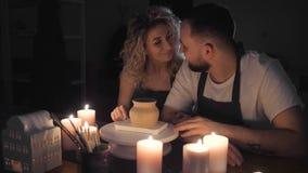 Couples romantiques dans l'amour fonctionnant ensemble dans l'atelier de studio de métier et dessiner un coeur sur un pot d'argil banque de vidéos