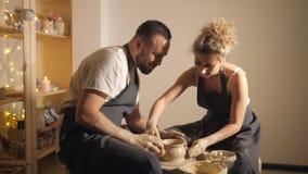 Couples romantiques dans l'amour fonctionnant ensemble sur la roue de potier et sculptant le pot d'argile, banque de vidéos