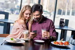 Couples romantiques dans l'amour utilisant le smartphone Photographie stock libre de droits