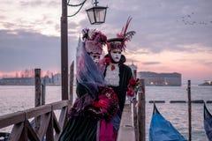 Couples romantiques dans le costume traditionnel et masques au lever de soleil, se tenant avec de nouveau à Grand Canal et le San images libres de droits