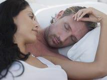 Couples romantiques dans le lit à colonnes Photographie stock libre de droits
