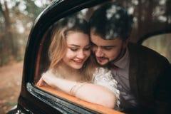 Couples romantiques de mariage de conte de fées embrassant et embrassant dans la forêt de pin près de la rétro voiture Photo libre de droits