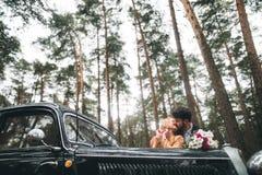 Couples romantiques de mariage de conte de fées embrassant et embrassant dans la forêt de pin près de la rétro voiture images libres de droits