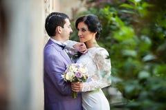 Couples romantiques de nouveaux mariés étreignant près du vieux mur de bâtiment Photos stock